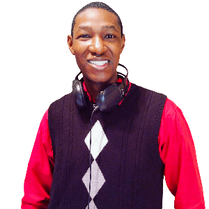 Aaron, also known as DJ Harris, posing for the camera with his headphones hanging around his neck. He is wearing a red button down dress shirt with a black sweater vest. The sweater vest has a diamond pattern down the middle
